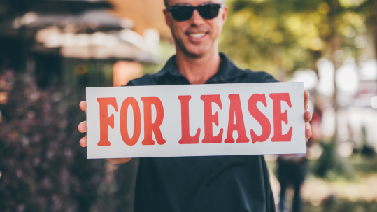 man holding for lease sign