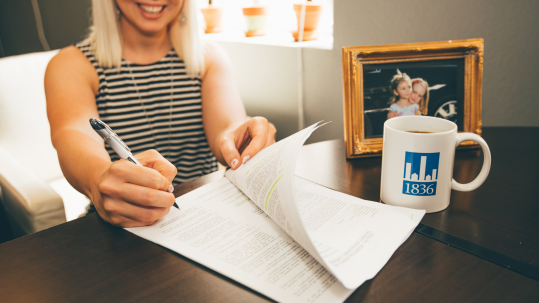 woman signing a lease document