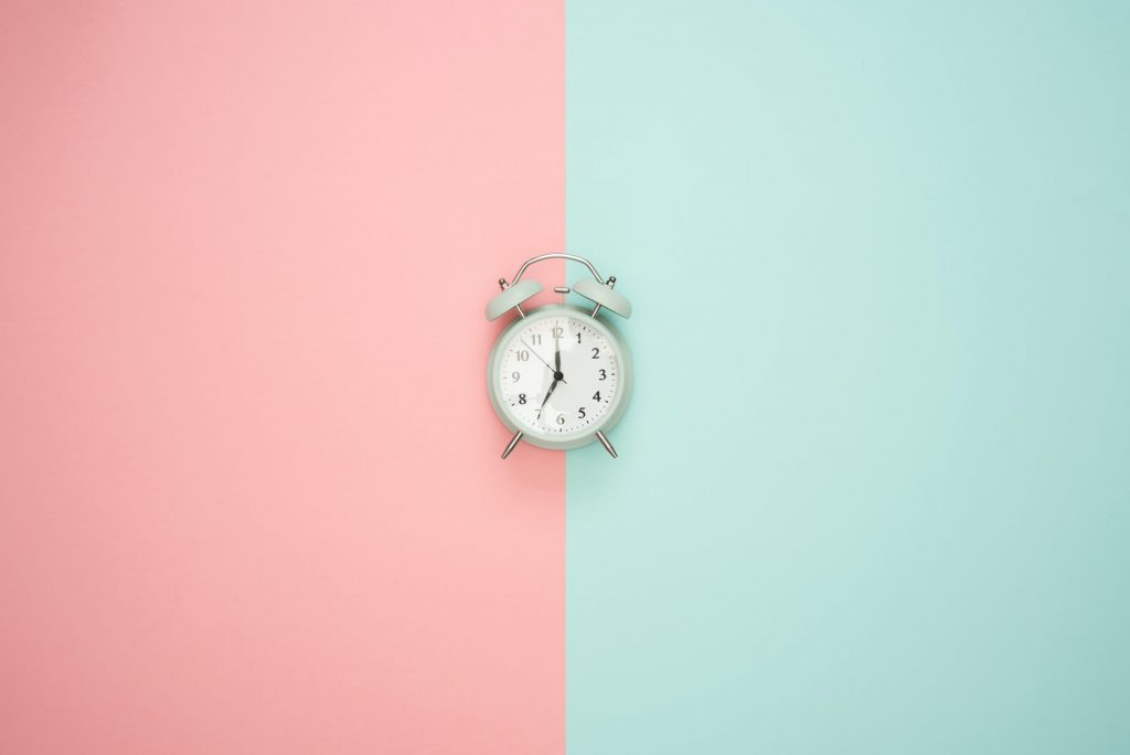 A clock on a pink and blue background.